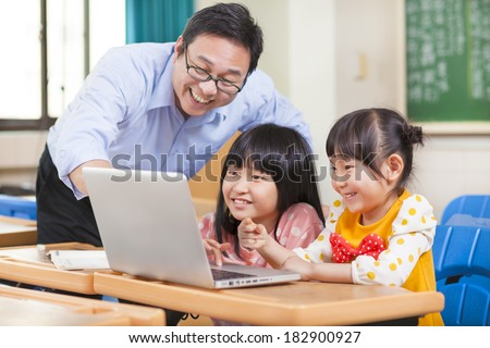 Teacher teaching  children with a laptop - stock photo