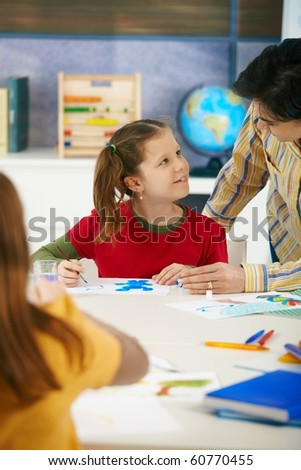Teacher teaching painting to elementary age children in classroom at primary school.? - stock photo