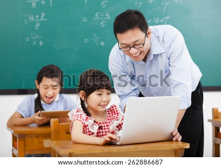 teacher teaching the computer with children  in classroom - stock photo