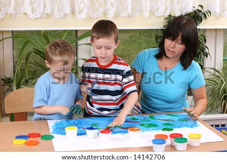 teacher two preschoolers and fingerpainting - education - stock photo