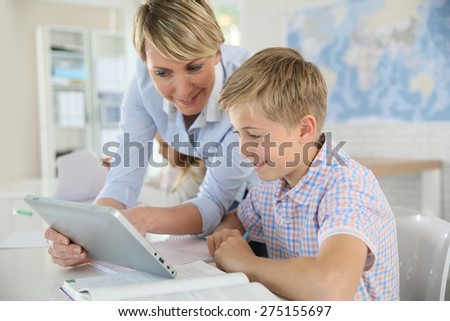 Teacher using digital tablet as educational tool in class - stock photo