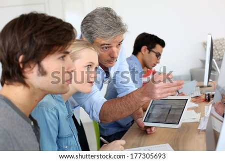 Teacher using digital tablet in school class - stock photo