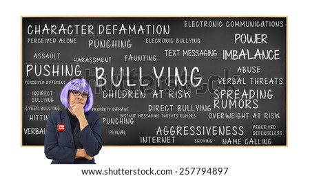 Teacher wearing stop bullying in front of Bullying Children At Risk: Power Imbalance, Pushing, Cyber Bullying, Assault, Harassment, Hitting, Verbal Abuse, Property Damage, Spreading Rumors - stock photo
