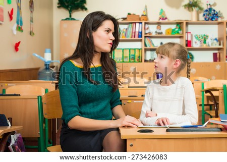 teacher with a student at a school desk - stock photo