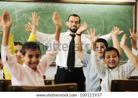 Teacher with boys and girls in school - stock photo