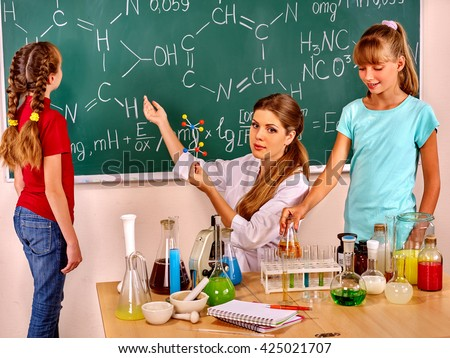 Teacher with children keeps flask and show on blackboard in chemistry class. - stock photo