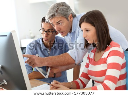 Teacher with group of students in class - stock photo