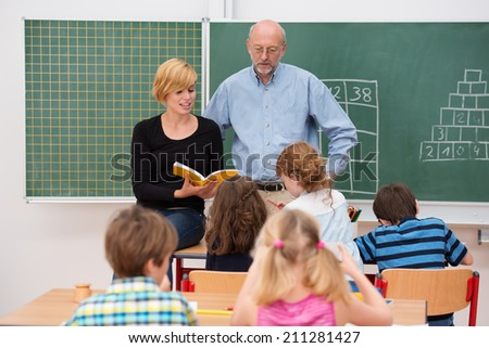 Teacher with his young attractive female teaching assistant standing in front of a class of small girls and boys as they discuss something from a textbook - stock photo