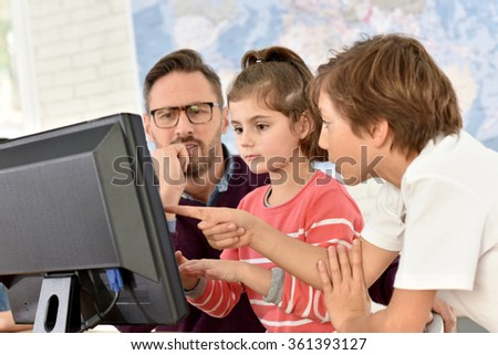 Teacher with kids in computing class - stock photo