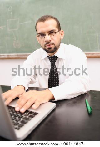Teacher with laptop at school classroom - stock photo