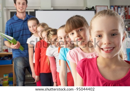 Teacher with line up of children in class - stock photo