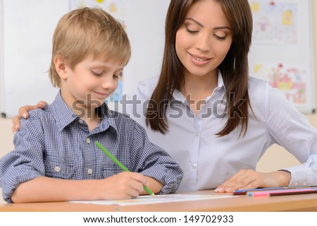 Teacher with pupil. Confident schoolboy writing something in note pad while sitting near his teacher - stock photo
