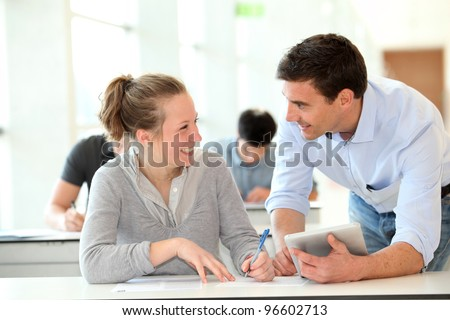 Teacher with student girl writing assignment - stock photo