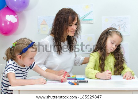 Teacher with two girls in kindergarten. - stock photo