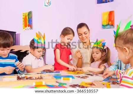 Teacher work with kids in art preschool class - stock photo
