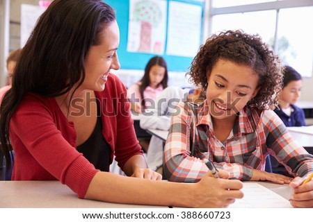 Teacher working with elementary school girl at her desk - stock photo