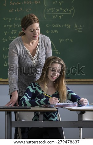 Teacher working with teen girl in a classroom - stock photo