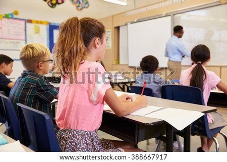 Teacher writing on the board in an elementary school class - stock photo