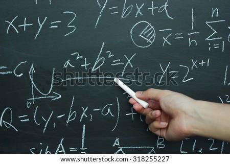 Teacher writing various high school maths formula on chalkboard. - stock photo