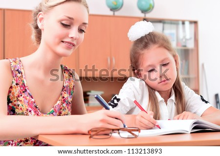 teachers are engaged with students, sitting next lesson explains - stock photo