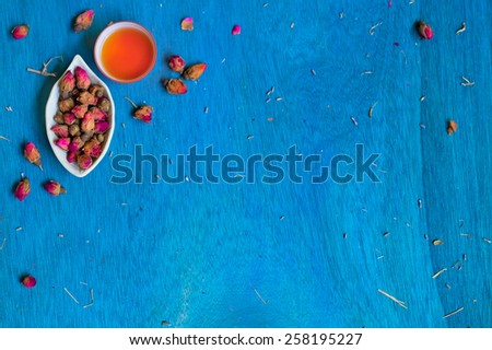 Teacup and small plate with rose buds on blue wooden background. Top view. Space for text. - stock photo