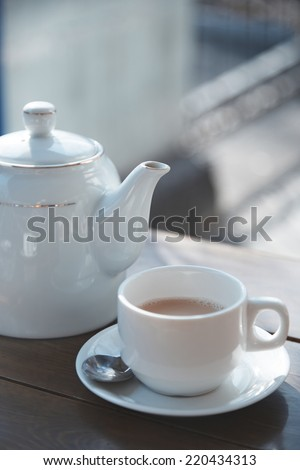 Teacup and teapot on the table at outdoors cafe - stock photo