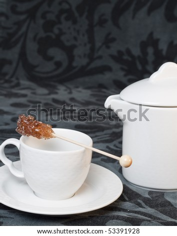Teacup with sugar stick and teapot - stock photo