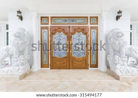 Teak wooden door with white lions statue. - stock photo