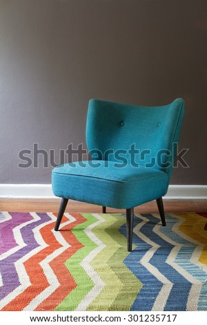 Teal blue retro armchair and colorful chevron pattern rug interior with grey wall - stock photo
