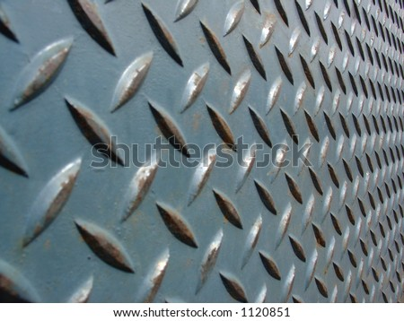 teal green worn diamond plate fading into the distance - stock photo