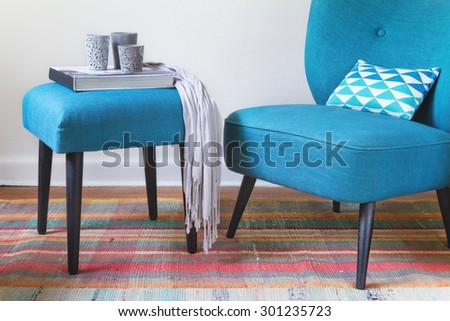 Teal retro armchair and colorful pink pattern rug interior with ottoman horizontal - stock photo
