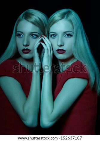 teal toned portrait of beautiful young blonde woman touching her reflection in mirror - stock photo