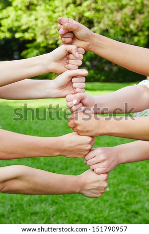 Team building tower in cooperation with their fists in nature - stock photo