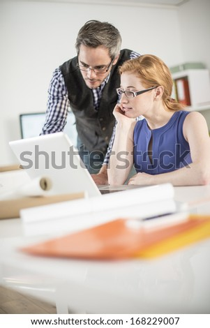 team discusses about a work project around a computer - stock photo