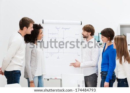 Team leader giving a presentation to his business team standing at a flipchart outlining the new project - stock photo