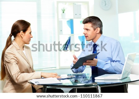 Team members discussing business document in office - stock photo