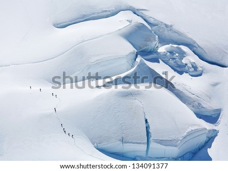 Team of alpinists traversing a dangerous glacier - stock photo