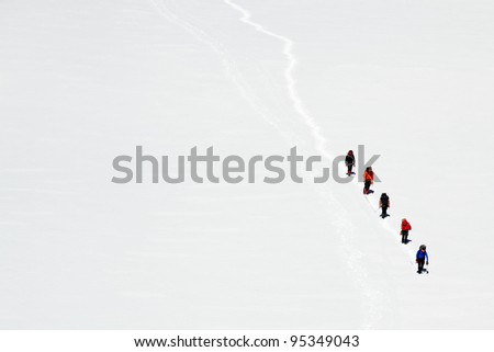 Team of alpinists traversing a glacier - stock photo