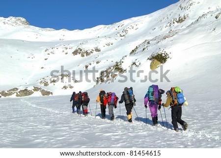 Team of alpinists traversing an iced lake in National Park Retezat, Romania - stock photo
