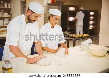 Team of bakers kneading dough in a commercial kitchen - stock photo