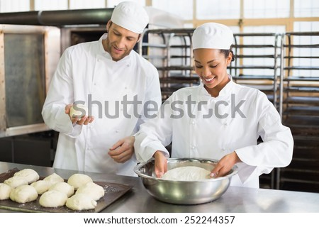 Team of bakers preparing dough in the kitchen of the bakery - stock photo