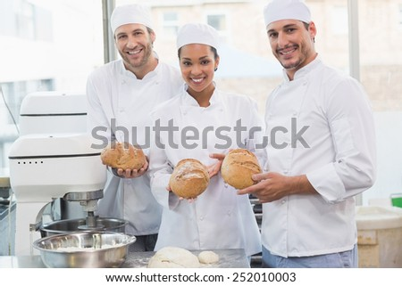 Team of bakers smiling at camera holding bread in the kitchen of the bakery - stock photo