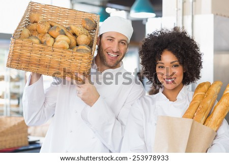 Team of bakers smiling at camera in the kitchen of the bakery - stock photo