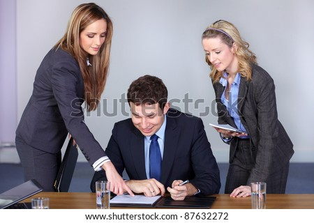 Team of 3 business people behind young businessman sitting and working on his laptop - stock photo