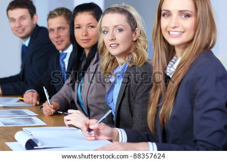 Team of 5 business people sitting at conference table and working on some calculations, focus on blonde female, second from right - stock photo