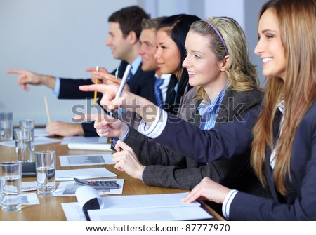 Team of 5 business people sitting at conference table point forward with their fingers, - stock photo