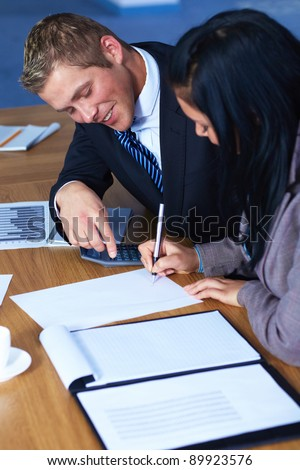 Team of 2 business people working on some documents, calculator and some documents on conference table - stock photo