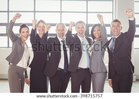 Team of businesspeople cheering with clenched fist in the office - stock photo