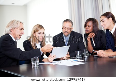 Team of businesspeople working together discussing in the office - looking at the notepad - stock photo