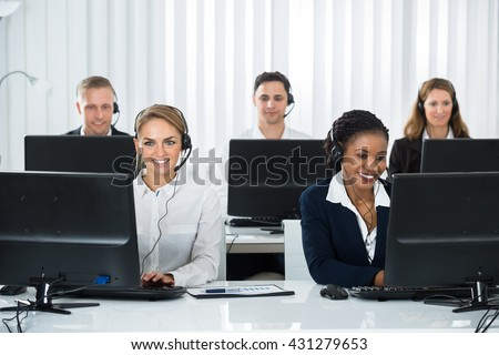 Team Of Call Center Operators Working On Computers At Workplace - stock photo
